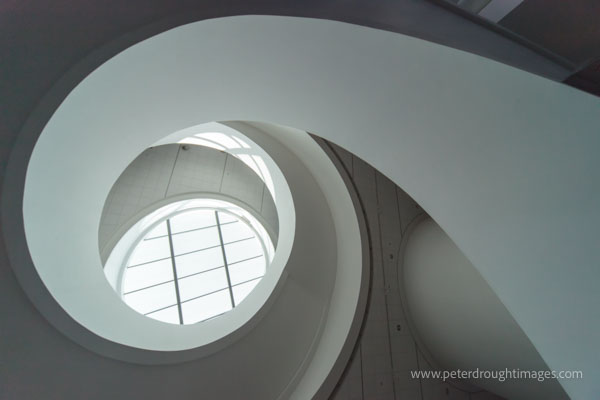 Photograph looking up a modern spiral stairwell towards a skylight.