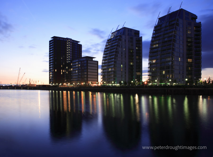 Architectural photography showing a group of modern apartment buildings at dusk with water in the foreground.