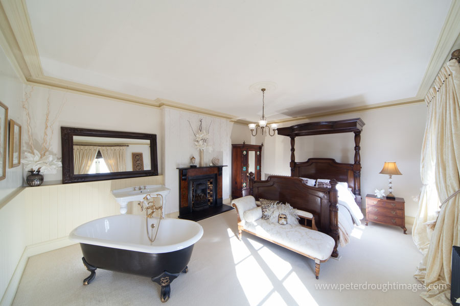 Property photography has been used to show a classically styled bedroom with bath feature.