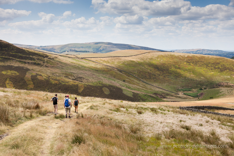 Picture of figures walking along a track with Pennine Hills in the background.